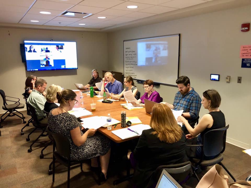 Image of WAVA Members around a conference table and joining on screen via WebEx